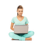 Chica joven que se sienta en el piso con el ordenador portátil Imagenes de archivo