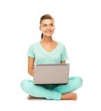 Chica joven que se sienta en el piso con el ordenador portátil Foto de archivo