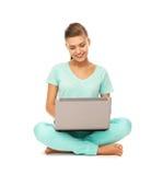 Chica joven que se sienta en el piso con el ordenador portátil Fotografía de archivo