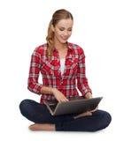 Chica joven que se sienta en el piso con el ordenador portátil Fotos de archivo