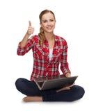 Chica joven que se sienta en el piso con el ordenador portátil Fotografía de archivo libre de regalías