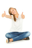 Chica joven que se sienta en el piso con los pulgares para arriba sobre el backgr blanco Fotografía de archivo libre de regalías