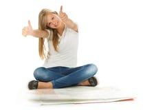 Chica joven que se sienta en el piso con los pulgares para arriba sobre el backgr blanco Imágenes de archivo libres de regalías