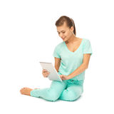 Chica joven que se sienta en el piso con PC de la tableta Fotos de archivo libres de regalías