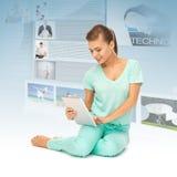 Chica joven que se sienta en el piso con PC de la tableta Imagen de archivo