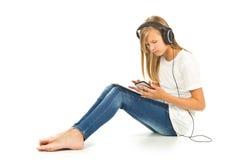 Chica joven que se sienta en el piso con PC, smartphone y h de la tableta Fotografía de archivo libre de regalías