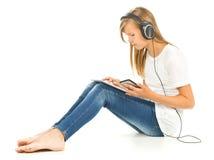 Chica joven que se sienta en el piso con PC, smartphone y h de la tableta Fotografía de archivo