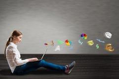 Chica joven que se sienta en el piso con un ordenador portátil Fotos de archivo