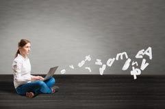 Chica joven que se sienta en el piso con un ordenador portátil Fotografía de archivo