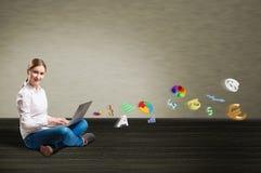 Chica joven que se sienta en el piso con un ordenador portátil Imagen de archivo libre de regalías