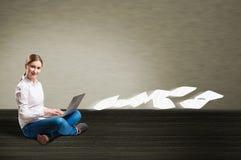 Chica joven que se sienta en el piso con un ordenador portátil Imágenes de archivo libres de regalías