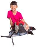 Chica joven que se sienta en el piso con una mochila IV Imagen de archivo