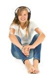 Chica joven que se sienta en el piso que escucha la música sobre los vagos blancos Imagen de archivo libre de regalías