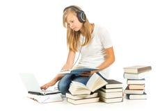 Chica joven que se sienta en el piso que estudia sobre el fondo blanco Imagen de archivo libre de regalías