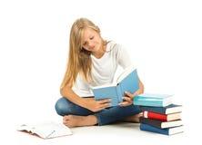 Chica joven que se sienta en el piso que lee sobre el fondo blanco Foto de archivo