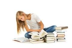 Chica joven que se sienta en el piso que lee sobre el fondo blanco Fotografía de archivo