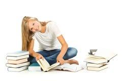 Chica joven que se sienta en el piso que lee sobre el fondo blanco Fotos de archivo libres de regalías