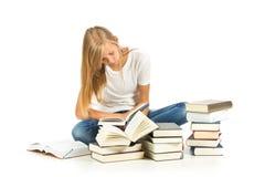 Chica joven que se sienta en el piso que lee sobre el fondo blanco Imagen de archivo libre de regalías