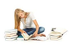 Chica joven que se sienta en el piso que lee sobre el fondo blanco Fotografía de archivo libre de regalías