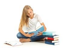 Chica joven que se sienta en el piso que lee sobre el fondo blanco Imagenes de archivo