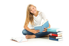 Chica joven que se sienta en el piso que lee un libro Imágenes de archivo libres de regalías