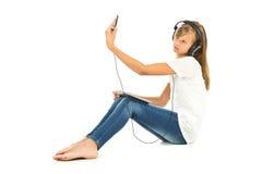 Chica joven que se sienta en el piso que toma un selfie con los auriculares Imagenes de archivo