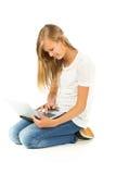 Chica joven que se sienta en el piso usando el ordenador portátil Fotografía de archivo