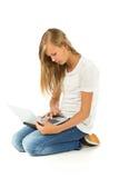 Chica joven que se sienta en el piso usando el ordenador portátil sobre el backgrou blanco Fotos de archivo