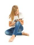 Chica joven que se sienta en el piso usando la PC de la tableta sobre el backg blanco Imagenes de archivo
