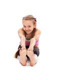 Chica joven que se sienta en el piso y estirar Imagen de archivo libre de regalías