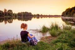Chica joven que se sienta en el riverbank La muchacha está en la naturaleza Admiración de la belleza del nature_ fotos de archivo libres de regalías