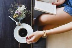 Chica joven que se sienta en el sofá de cuero beige y que lee un libro Fotografía de archivo libre de regalías