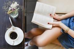 Chica joven que se sienta en el sofá de cuero beige y que lee un libro Fotografía de archivo
