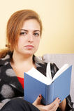 Chica joven que se sienta en el sofá y que sostiene un libro Foto de archivo libre de regalías