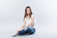 Chica joven que se sienta en el suelo Fotos de archivo libres de regalías
