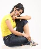 Chica joven que se sienta en el suelo Foto de archivo