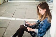 Chica joven que se sienta en estudiar de la yarda del campus de la universidad Fotos de archivo