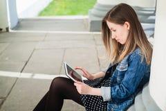 Chica joven que se sienta en estudiar de la yarda del campus de la universidad Fotografía de archivo libre de regalías