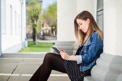 Chica joven que se sienta en estudiar de la yarda del campus de la universidad Fotografía de archivo