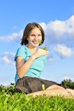 Chica joven que se sienta en hierba Imagenes de archivo
