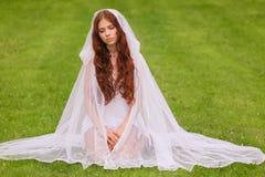 Chica joven que se sienta en hierba fotografía de archivo