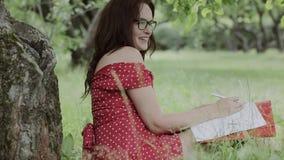 Chica joven que se sienta en hierba debajo de árbol y que escribe notas metrajes