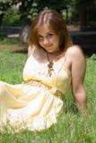 Chica joven que se sienta en hierba verde en parque Fotos de archivo libres de regalías