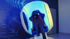 Chica joven que se sienta en la atracción de la realidad virtual y que siente asustadiza Imagen de archivo libre de regalías