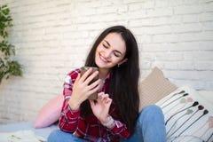 Chica joven que se sienta en la cama y el contenido de observación en el teléfono elegante imágenes de archivo libres de regalías