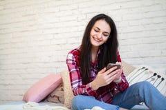Chica joven que se sienta en la cama y el contenido de observación en el teléfono elegante fotos de archivo