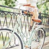 Chica joven que se sienta en la cerca cerca de la bici del vintage en el parque Fotos de archivo