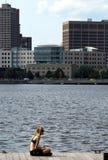 Chica joven que se sienta en la cubierta al lado de Charles River en Boston imagen de archivo