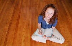 Chica joven que se sienta en la escritura del suelo Imágenes de archivo libres de regalías