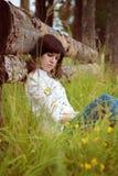 Chica joven que se sienta en la hierba Imagen de archivo libre de regalías